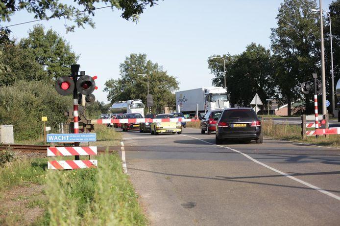 Auto's slalommen tussen gesloten slagbomen door na een spooraanrijding waardoor de spoorbomen gesloten blijven.