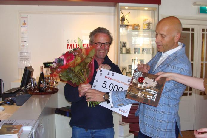 Arjen Cuijpers, voorzitter van het stedelijk museum Vianen, 'overvalt' Maarten Kerkhof met de mededeling dat hij de 5000ste bezoeker is van de tentoonstelling Miauw!