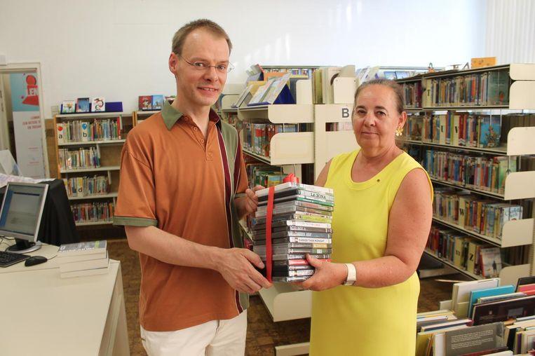 OCMW-raadslid Wim Durang overhandigt de stapel films aan bibliothecaris Els Cleymans.