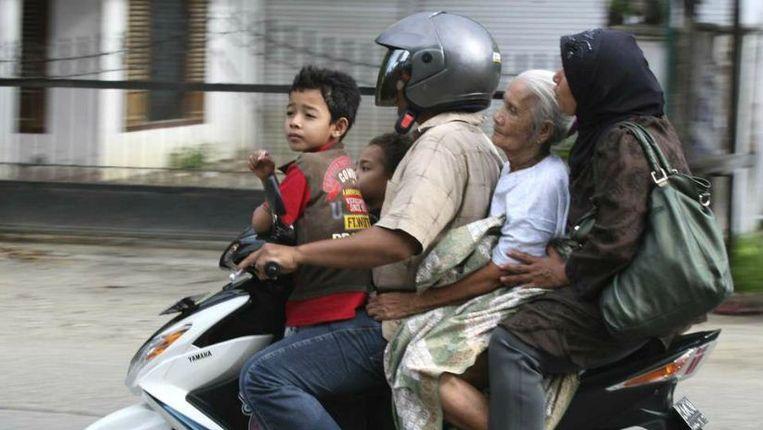 Een Atjeeër vervoert zijn familie per brommer. De vrouw zonder hoofddoek zit zoals het bestuur van Lhokseumawe het graag ziet. Beeld reuters