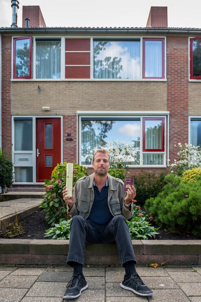 Bert van Driel voor het huis van zijn ouders in Bergambacht. In zijn handen de spullen die hij meenam uit Sint-Maarten: zijn universitaire bul en zijn paspoort.