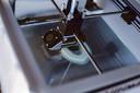Een 3D-printer is bezig met een mondbitje. Het printproces duurt een half uur tot een uur