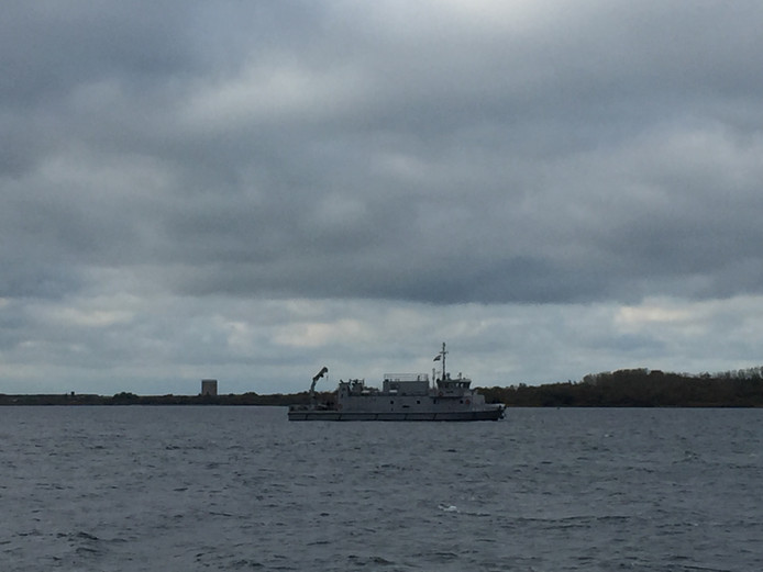 Het marineschip verderop op het water.