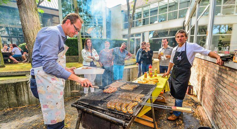 Burgemeester Youro Casier, chef barbecue van dienst, schept enkele braadworsten van het rooster.