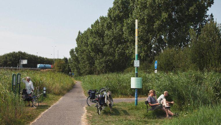 Op de Durgerdammerdijk laat een 5 meter hoge paal zien hoe diep het veenweidelandschap hier al is gezonken. Beeld Maarten Boswijk