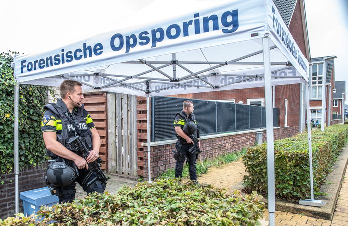 Politie houdt zwaar bewapend tijdens het forensische onderzoek het huis en de buurt in de gaten.