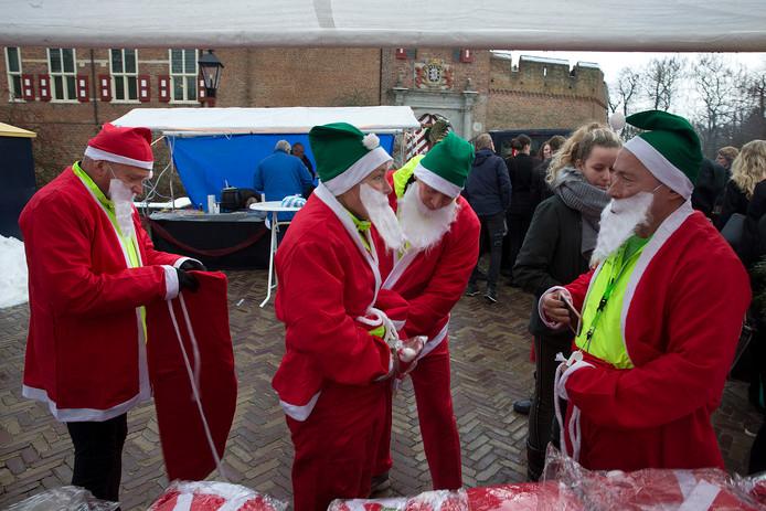 Kerstmannen maken zich klaar voor de start van de Santa Funwalk. Foto Theo Kock