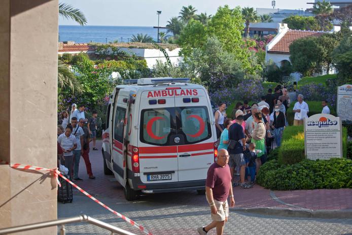 Een ambulance voor het getroffen hotel Acapulco in Kyrenia. Geschrokken toeristen wachten buiten.