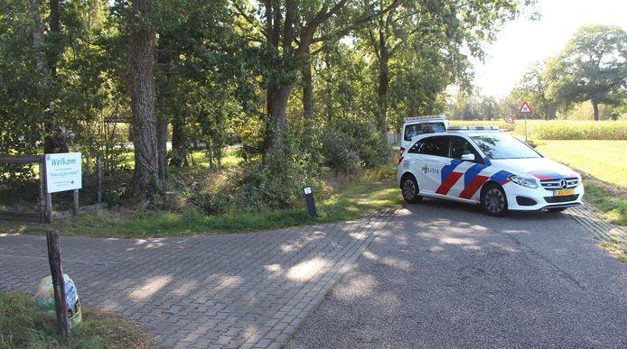 Een politieauto staat dwars op de Karelsdijk geparkeerd. Wie van het vakantiepark de weg op wil, kan alleen weg via de registratietent van het project Ariadne.