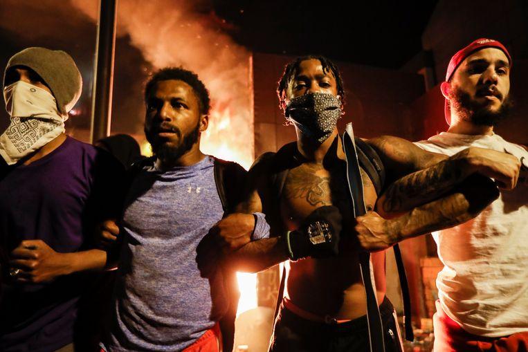 Demonstranten voor het brandende politiebureau dat donderdagnacht werd bestormd.  Beeld AP