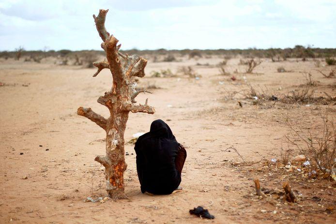 Een zwangere Somalische vrouw zit bij een boomstam in een vluchtelingenkamp. Wetenschappers zeggen dat klimaatverandering het aantal asielzoekers in de EU enorm gaat verhogen.