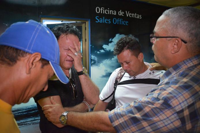 Nabestaanden van de reizigers aan boord van het gecrashte vliegtuig zoeken op het vliegveld steun bij elkaar.