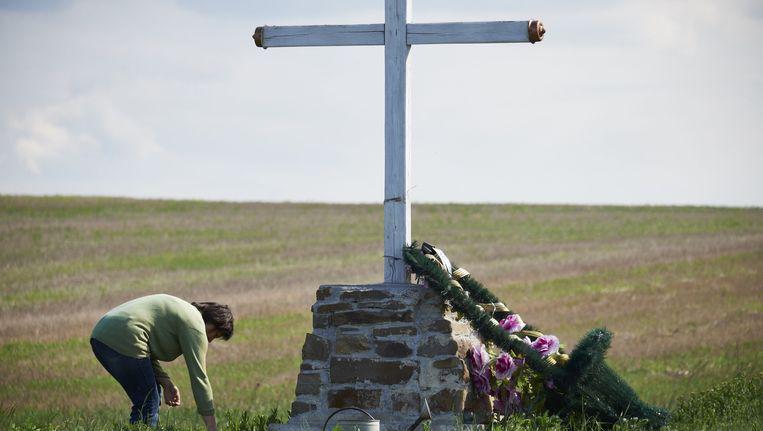 Een vrouw verzorgt het kruis bij de burnsite van vlucht MH17 van Malaysia Airlines. Rond de rampplek in Oost-Oekraine zijn veel van dit soort gedenktekenen te vinden. Beeld anp
