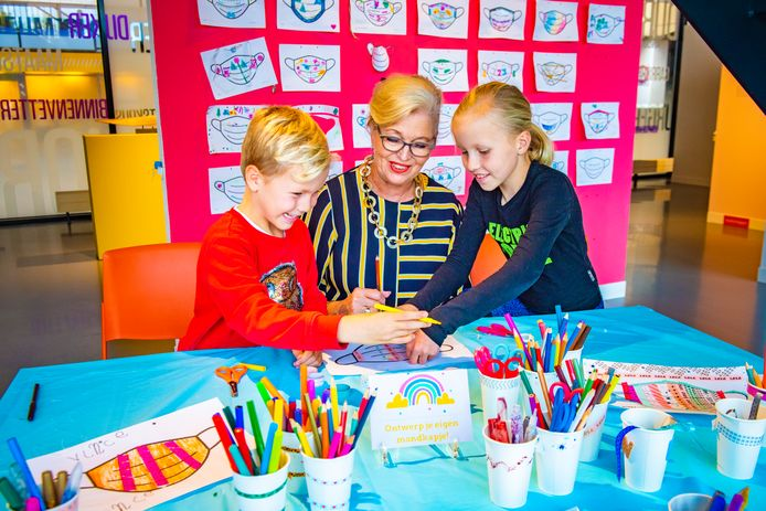 Vince (6) en Julie (9) maken samen met oma Corrie Buren mondkapjes bij Museum De Voorde.