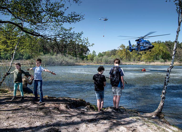 Een helikopter uit Duitsland haalt water bij een ven in de buurt van de grote brand. Beeld Koen Verheijden