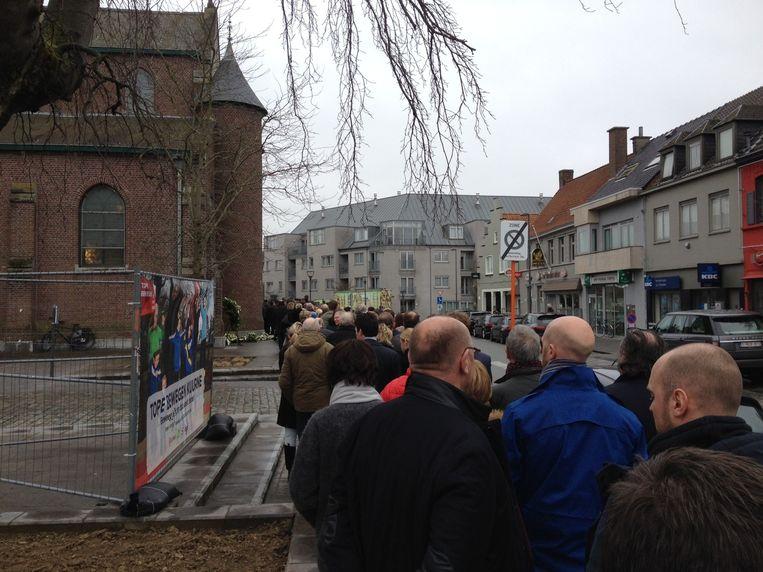 Mensen schuiven aan om de kerk binnen te gaan.