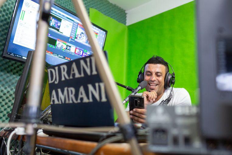 Dj Rani Amrani praat met zijn Iraans-Joodse luisteraars in de studio. Beeld Geert van Kesteren
