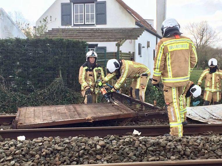 De brandweer verwijdert de omgewaaide paardenstal van de sporen.