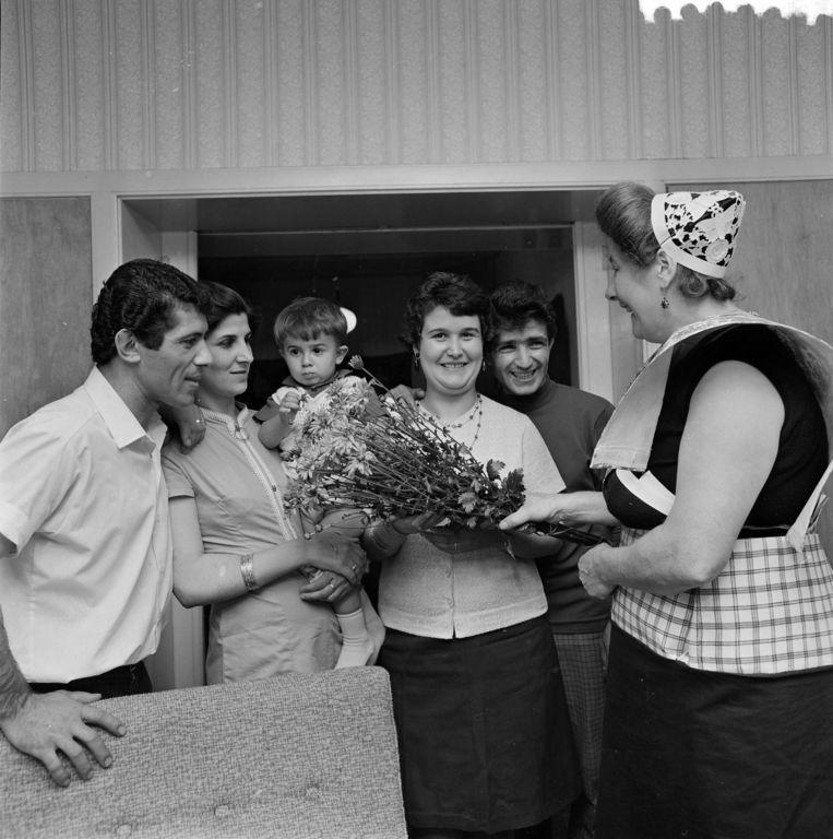 1968: Twee Turkse gastarbeiders in Spakenburg zijn herenigd met hun vrouwen. Een in klederdracht gestoken buurtgenote brengt een bos bloemen. Beeld anp