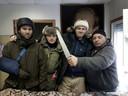 Jelle Brandt Corstius (tweede van rechts) en reisgenoten Aldo van den Broek en Fabian Hahne bezoeken een slager op de markt in Tynda.