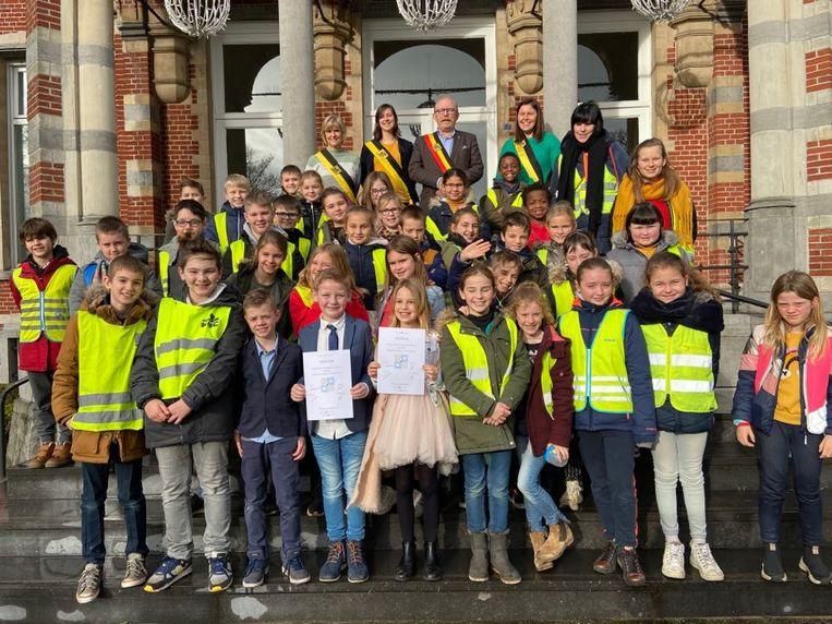 De leerlingen van het derde leerjaar van basisschool Sint-Calasanz met burgemeester en een aantal schepenen.