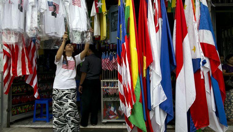 Een Birmese vrouw hangt shirts met Amerikaanse vlaggen op in Rangoon. Beeld getty