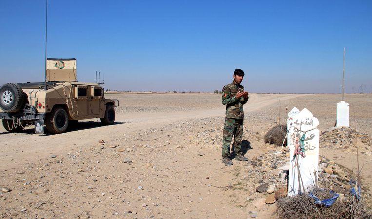 Een Afghaanse soldaat bidt bij een graf. Ondanks een akkoord tussen de VS en de Taliban laaide het geweld weer op. Beeld EPA
