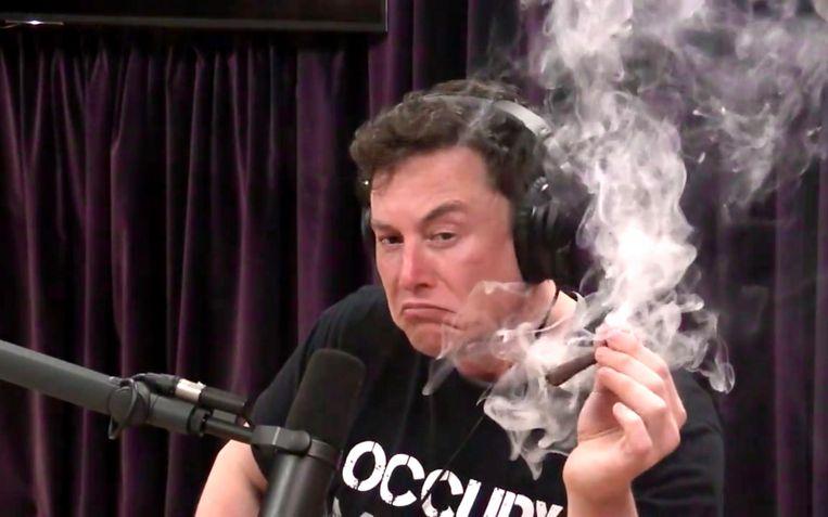 Tesla's topman Elon Musk rookt een vermoedelijke joint (of 'blunt') tijdens een Amerikaans video-interview. Beeld