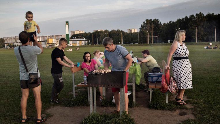 Etnische Russen houden een picknick in Plavnieki, een buurt in Riga waar overwegend Russen wonen. Beeld Yuri Kozyrev/ Noor