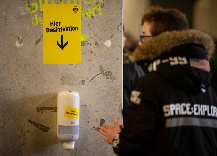 Een fan van Borussia Dortmund gebruikt desinfectiemiddel in een Duits stadion