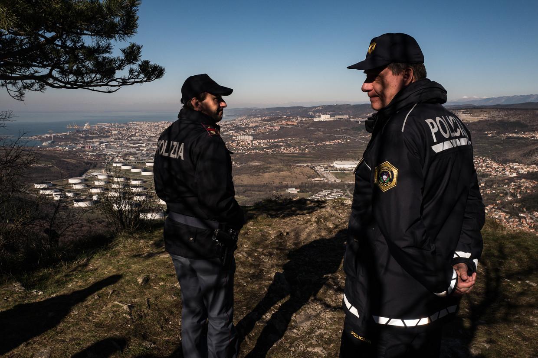 Een Italiaanse en een Sloveense grenswacht patrouilleren, met uitzicht op Triëst, de Italiaanse stad die migranten hopen te bereiken. Beeld Nicola Zolin