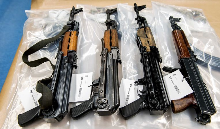 Pistolen, revolvers, automatische wapens, munitie en handgranaten liggen uitgespreid op een tafel in het kantoor van Korps Landelijke Politiediensten. De wapens zijn aangetroffen in een opslagruimte in Nieuwegein.  Beeld ANP