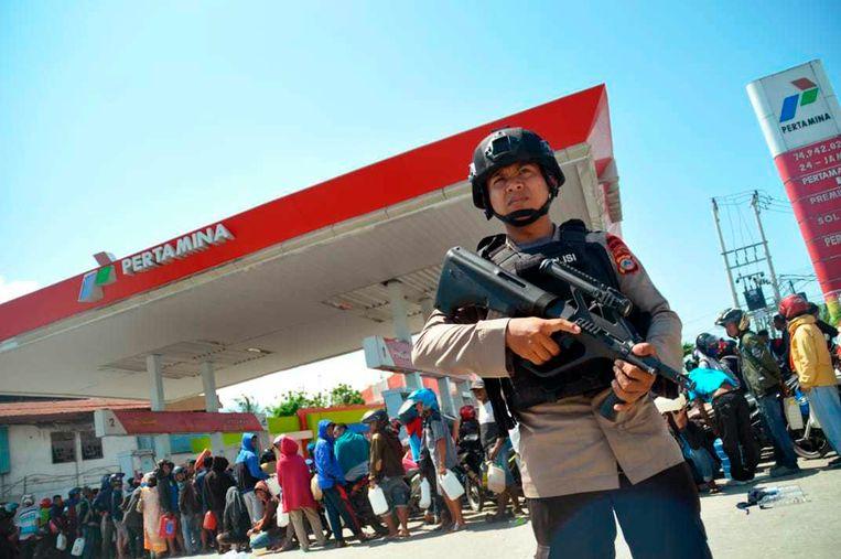 Een politieman bewaakt een benzinestation in de stad Palu. Beeld AP