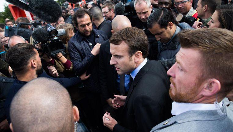 Emmanuel Macron te midden van stakende werknemers van Whirlpool in Amiens die hem uitfluiten, 26 april. Whirlpool verplaatst de fabriek volgend jaar naar Polen, waardoor 400 werknemers hun baan verliezen. Beeld getty