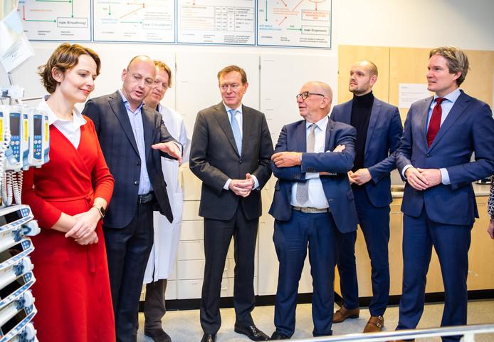 Minister Bruins (gevouwen handen) op werkbezoek in het Spijkenisse Medisch Centrum. Rechts naast hem staan bestuurder Paul van der Velden, wethouder Wouter Struijk en burgemeester Foort van Oosten. Links in de rode jurk medisch manager Martine den Otter van Huisartsenposten Rijnmond.