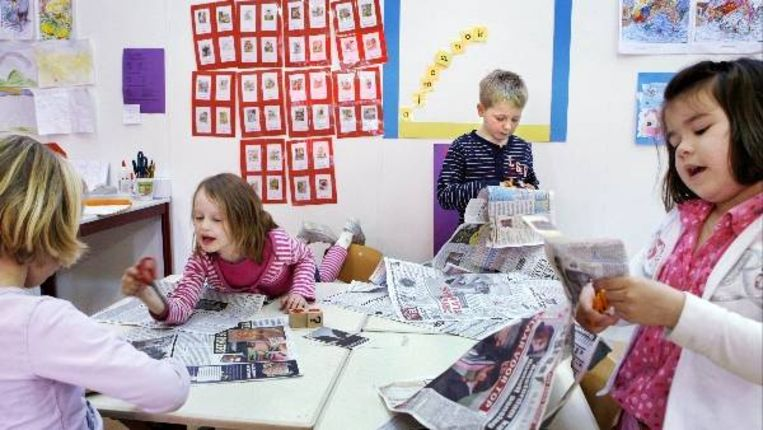 Kinderen van groep 3 op de openbare Jenaplan basisschool de Imenhof knippen en lezen de krant. ( Jorgen Caris, Trouw) Beeld