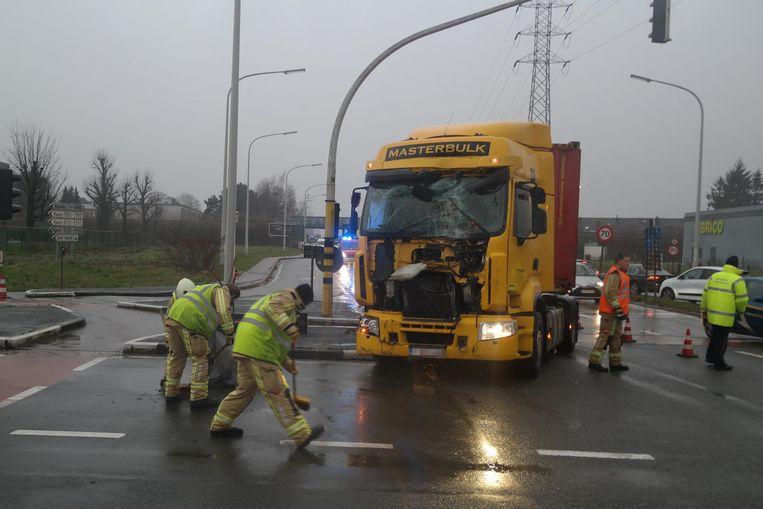 De hulpdiensten zijn druk bezig de baan op te ruimen na het zware ongeluk, waarbij de chauffeur in de vrachtwagen zwaargewond raakte.