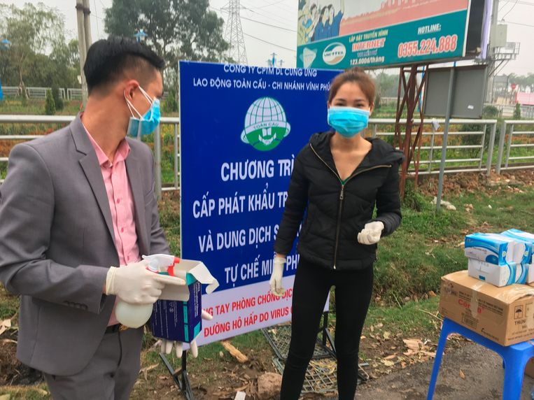 Gezondheidsmedewerkers bij een waarschuwingsbord over Covid-19 aan een controlepost bij het betreden van Son Loi.