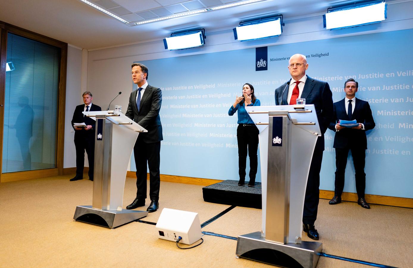 Premier Rutte en de ministers Martin van Rijn (geheel links), Ferd Grapperhaus en Hugo de Jonge (geheel rechts) maandag tijdens hun persconferentie.