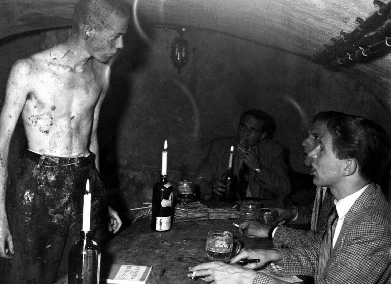 Ontgroening van een feut waarbij bierdrinkende ouderejaars hem in een kelder van achter een door kaarsen verlichte tafel toeschreeuwen, Nederland, 1962. Beeld Hollandse Hoogte / Spaarnestad Photo