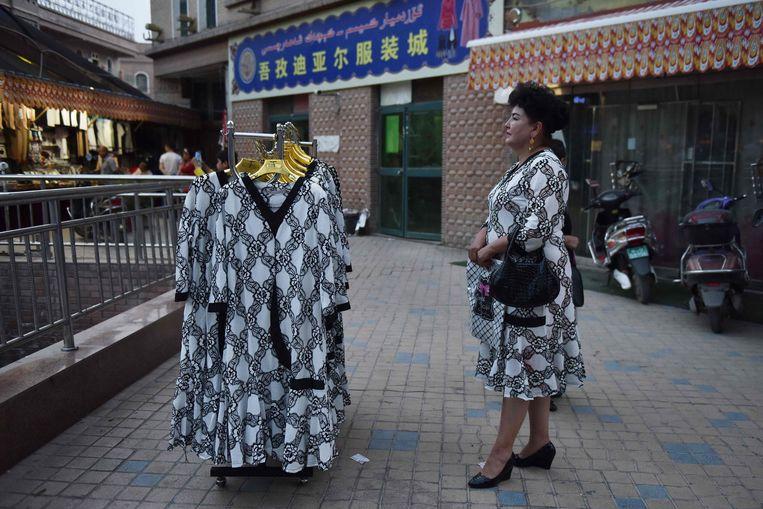Een Oeigoerse kledingverkoopster wacht op klanten bij een markt in Kashgar, in de noordwestelijke Chinese regio Xinjiang. De autoriteiten regeren in het gebied met ijzeren vuist. Toeristen flaneren er op steenworp afstand van interneringskampen.     Beeld AFP