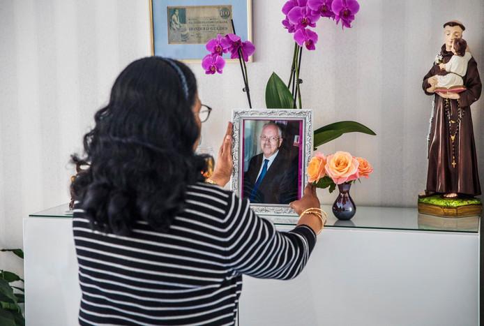 Netty Reijsbergen bekijkt de foto van haar man, die op de mantel staat.