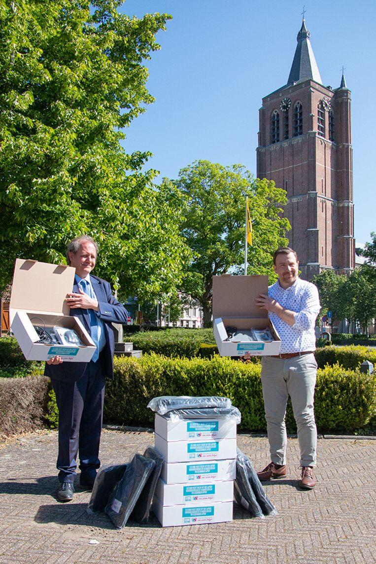 Burgemeester Matheï (rechts) overhandigt de laptops aan Knevels, directeur van BuSO Sint-Elisabeth Wijchmaal.
