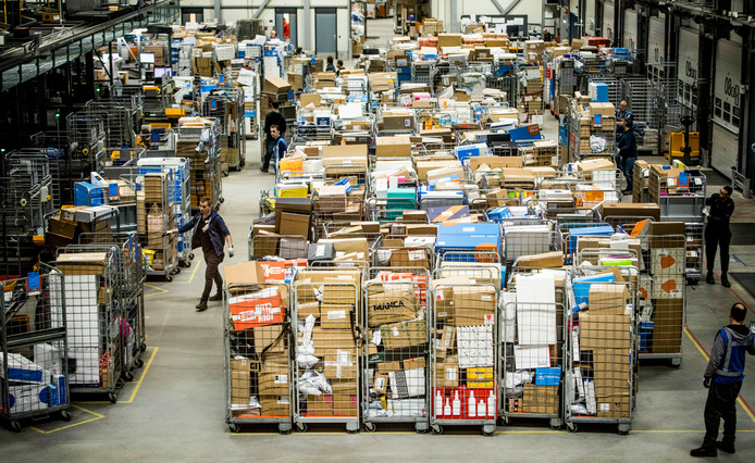 Medewerkers van PostNL sorteren pakketjes in het pakkettensorteercentrum. De periode rond Sinterklaas is een van de drukste periodes van het jaar.
