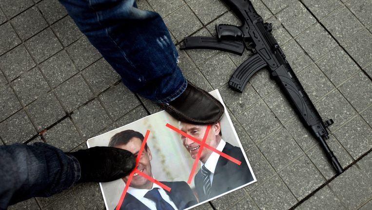 Turkse en Syrische demonstranten staan op de portretten van de Russische president Medvedev en premier Poetin, voor het Russische consulaat in Istanbul. Beeld EPA