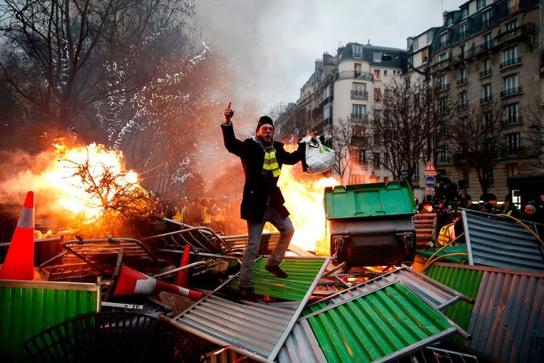 Een demonstrant op een door de gele hesjes opgeworpen barricade. Beeld AFP