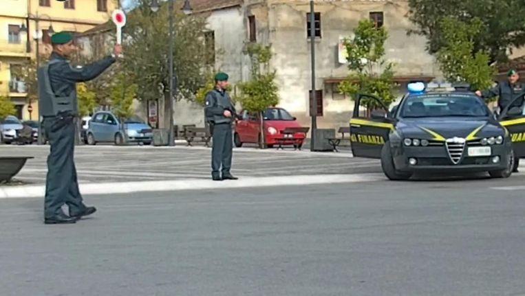 Leden van de carabinieri begeleiden een konvooi van verdachten. Beeld
