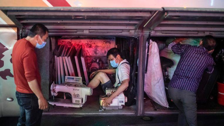 Een arbeidsmigrant die in Guangzhou (de hoofdstad van Guangdong) niet meer aan de slag kan, wurmt zich met zijn naaimachines in de bus op weg naar zijn geboorteprovincie Hubei. Beeld EPA
