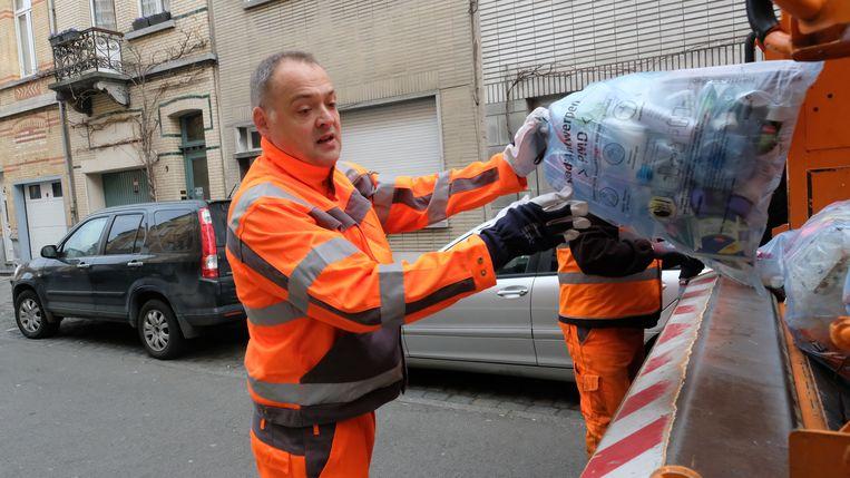 Fons Duchateau zwiert een zak in de vuilniskar.