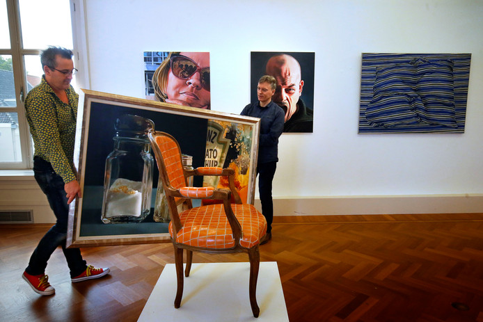 Jack van Mildert (l) en Freek van der Vliet zijn druk bezig met het inrichten van de expositie met realistische schilderijen.